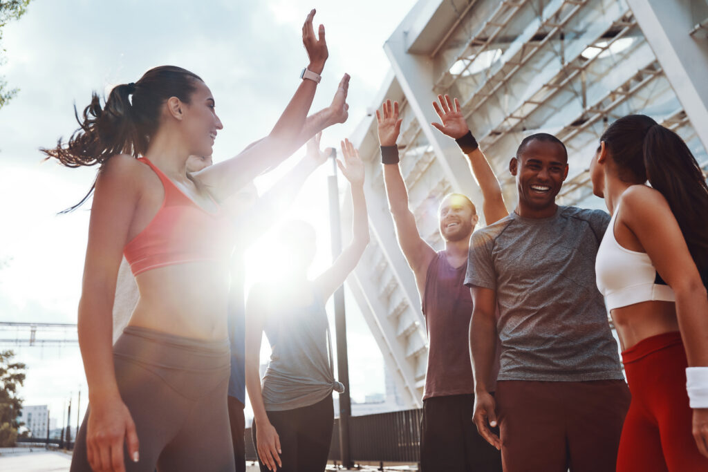 Group of young people in sports clothing giving each other high five and smiling while doing calisthenics