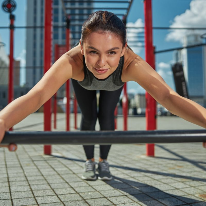 Close up of female doing pushups outside on a bar
